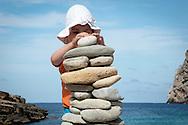 BORD DE MER AVEC PIERRES <br /> Un petit enfant joue avec des cailloux <br /> paysage nature equilibre kern illustration zen<br /> Empilement de cailloux<br /> <br /> <br /> (PHOTO-GENIC.CH/ OLIVIER MAIRE)