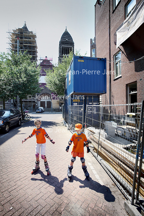 Nederland, Amsterdam , 28 juni 2010..Renovatieperikelen bij Jacob Obrechtstraat en bij appartementen Palestrinastraat..Renovation in Amsterdam with two children in orange, suppporters of the Dutch football team.