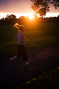 Setting sun with jogger in Ruskin Park in the borough of Lambeth, south London.