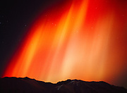 Brilliant orange, red and yellow aurora above Arkose Ridge during geomagnetic storm on the night of November 5, 2001, Talkeetna Mountains, Alaska.