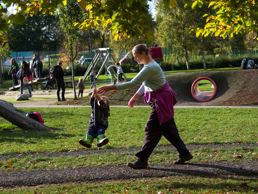 A woman pushes her child on the swing in a playground in Pittville Park, Cheltenham, UK, as the country continues to endure the Coronavirus pandemic