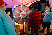 AARP's Richard Gellman, left, and Robert Harvey, right, work the prize wheel at the AARP Block Party at the Albuquerque International Balloon Fiesta in Albuquerque New Mexico USA on Oct. 8th, 2018.