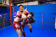 """18 DECEMBER 2104 - BANGKOK, THAILAND: An informal workout and sparring session at the Kanisorn gym. The Kanisorn boxing gym is a small gym along the Wong Wian Yai - Samut Sakhon train tracks. Young people from the nearby communities come to the gym to learn Thai boxing. Muay Thai (Muai Thai) is a Thai fighting sport that uses stand-up striking along with various clinching techniques. It is sometimes known as """"the art of eight limbs"""" because it is characterized by the combined use of fists, elbows, knees, shins, being associated with a good physical preparation that makes a full-contact fighter very efficient. Muay Thai became widespread internationally in the twentieth century, when practitioners defeated notable practitioners of other martial arts. A professional league is governed by the World Muay Thai Council. Muay Thai is frequently seen as a way out of poverty for young Thais and Muay Thai camps and schools are frequently crowded. Muay Thai professionals and champions are often celebrities in Thailand.     PHOTO BY JACK KURTZ"""