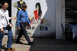 © Licensed to London News Pictures. 23/07/2021. LONDON, UK.  People pass a mural of Amy Winehouse by street artist bambi in Bayham Street in Camden Town on the tenth anniversary of the late singer's death.  Photo credit: Stephen Chung/LNP