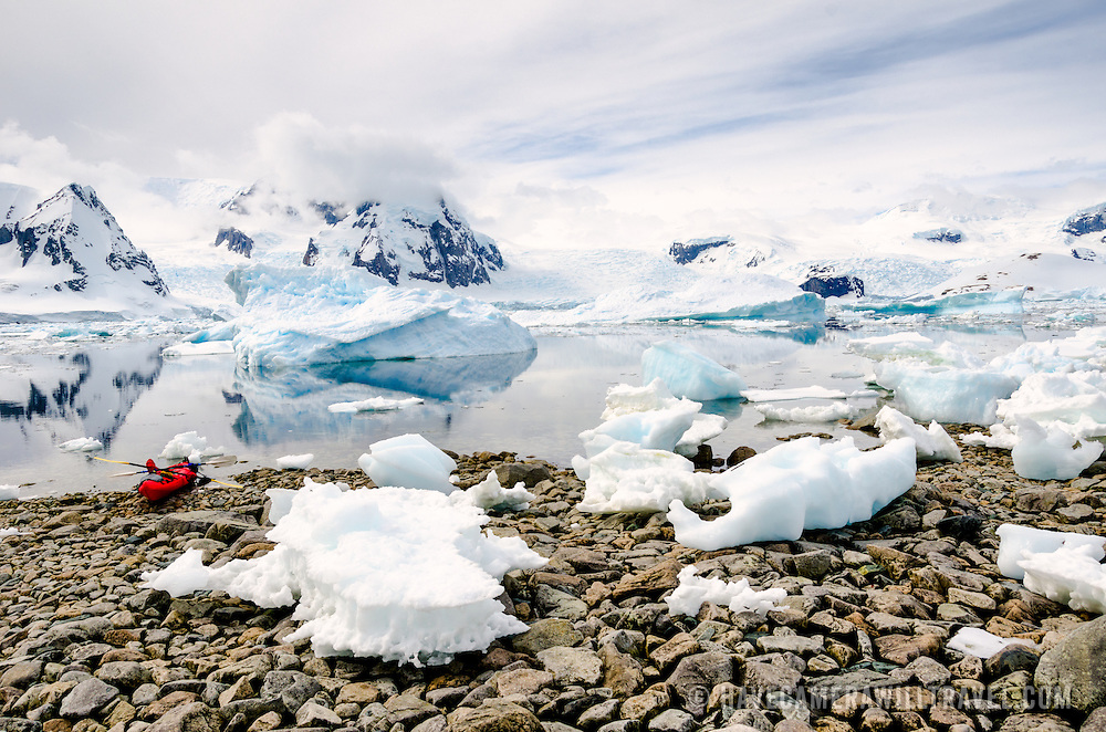 A kayak is pulled up on the rocky beach at Cuverville Island on the Antarctic Peninsula, with the mountains in the background reflecting on the calm water.