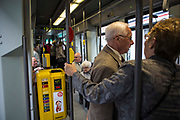 Elderly people travel onboard an electric tram operated by De Lijn in Ghent, Belgium.