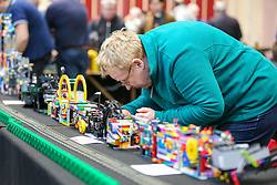 © Licensed to London News Pictures. 17/01/2020. London, UK. A member of Brickish tends to a lego models at the London Model Engineering Exhibition at Alexandra Palace as enthusiasts and hobbyists visit the annual show in north London. Clubs and societies are exhibiting spectrum of modelling from traditional model engineering, steam locomotives and traction engines through to the more modern gadgets including trucks, boats, aeroplanes and helicopters with nearly 2,000 models constructed by their members. Photo credit: Dinendra Haria/LNP