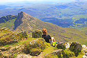 Person enjoying view from the summit of Mount Snowdon, Gwynedd, Snowdonia, north Wales, UK looking south east