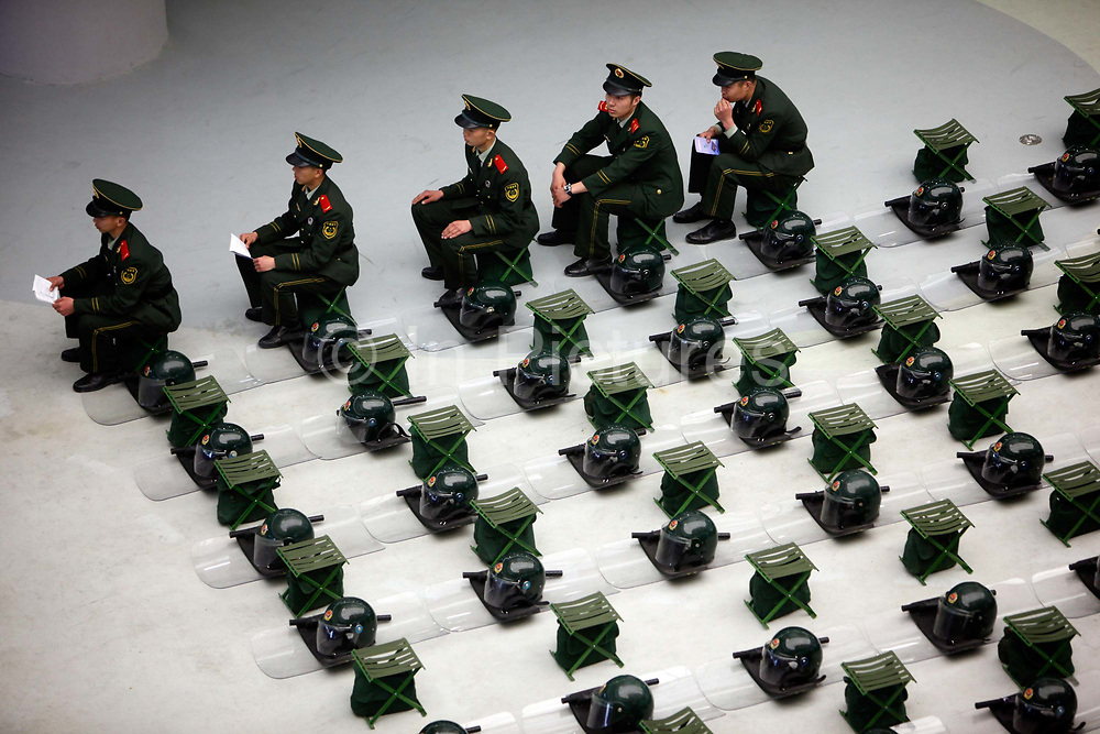 Members of the Armed Police sit amongst neat roles of riot gears at the site of the 2010 World Expo in Shanghai, China on 23 April 2010. The expo will begin on May 01. Shanghai eventually spent some 40 billion usd in developing the expo site and related infrastructure, and saw a record breaking 70 million visitors, the site has seen limited use after the end of the expo. Investment in government infrastructure and real estate spending have surpassed foreign trade as the biggest contributor to China's growth, fueling fears of an economic slow down triggered by the debt burden.