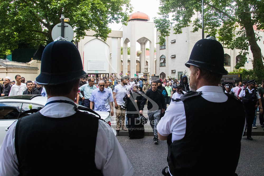 London, June 23rd 2017. Police are in evidence as Muslim worshippers gather for Friday Prayers at London Central Mosque in Regents Park, following the suspected terror attack in the early Hours of Monday June 19th when Darren Osbourne, 47, from Cardiff, now charged with terrorism-related murder, is alleged to have run down a group of Muslims in Finsbury Park. PICTURED: Met Police officers keep watch as Muslims leave the mosque.