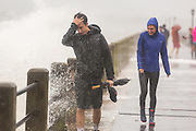 Tourists are soaked by massive waves splashing over the historic Battery as Hurricane Joaquin brings heavy rain, flooding and strong winds as it passes offshore October 3, 2015 in Charleston, South Carolina.