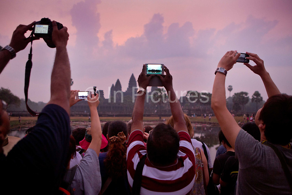 Tourists using digital devices - iphones, tablets, ipads, cameras -  photograph the dawn at Angkor Wat; waiting to see the light come up over the main temple of Angkor.