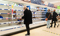© Licensed to London News Pictures. 23/12/2020. London, UK. Shoppers look at nearly empty shelves of meat products in Sainsbury's supermarket in north London, just two days before Christmas day. A number of supermarkets have warned that some items may run low this week. France has ended its ban on the UK arrivals and has reopened its borders with the UK under the condition of a negative COVID-19 test. It is expected that the backlog of lorries wishing to travel to Europe will take days to clear, and could impact further on food supplies. Photo credit: Dinendra Haria/LNP