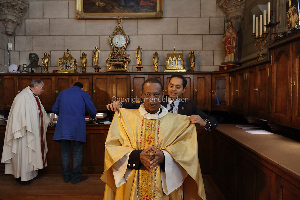 Patrick Kollannur, sacristan, adjusting the chasuble of the priest who will perform midday mass, in the sacristy at the Cathedrale Notre-Dame de Paris, or Notre-Dame cathedral, built 1163-1345 in French Gothic style, on the Ile de la Cite in the 4th arrondissement of Paris, France. In the sacristy, preparations are made for services and mass, and books and robes are stored. Picture by Manuel Cohen