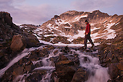 Hiker Doug Faust crosses over a cascade at the outlet of a lake in an alpine basin used as base camp for climbs of Glacier Peak in Glacier Peak Wilderness, Washington.