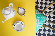 Tea pot and cup on a yellow table on 07th April 2017 in Dublin, Republic of Ireland. Dublin is the largest city and capital of the Republic of Ireland.