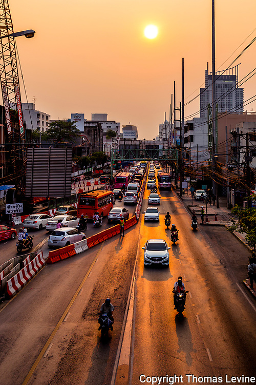 Construciton traffic in Bangkok close to sunset with sun and lgiht reflected on the highway.