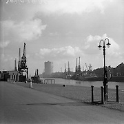 """05/03/1957<br /> Scenes on the Liffey River, Dublin from the Custom House. View of ships and cranes along the quays. Closest ship might be called """"The Last Chance""""."""