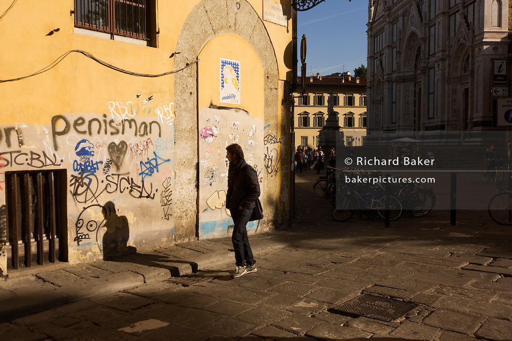 Local passing graffiti street corner and tourist kiosk near Florence's Piazza Santa Croce. It is a bright morning and the sunshine illuminates the yellow wall that has been covered at ground level by the scrawls of graffiti by local youths - a facet of every corner of the city's medieval architecture.