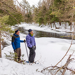 A couple snowshoeing next to the Crooked River at Western Foothills Land Trust's Twin Bridges Preserve in Otisfield, Maine.