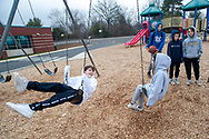 Drew Smith (left) and Brianna Muntz share a laugh as they swing on the swingset in the playground after their school was closed for the day because of a possible coronavirus threat Friday, March 06, 2020 at Titus Elementary School in Warrington, Pennsylvania. Five Central Bucks School District schools were closed as a precaution against coronavirus. WILLIAM THOMAS CAIN / For The Inquirer