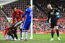 16th April 2017 - Premier League - Manchester United v Chelsea - Eric Bailly of Man Utd is helped to his feet by Diego Costa of Chelsea as teammates Marcos Rojo (C) and Man Utd goalkeeper David De Gea (R) look on - Photo: Simon Stacpoole / Offside.