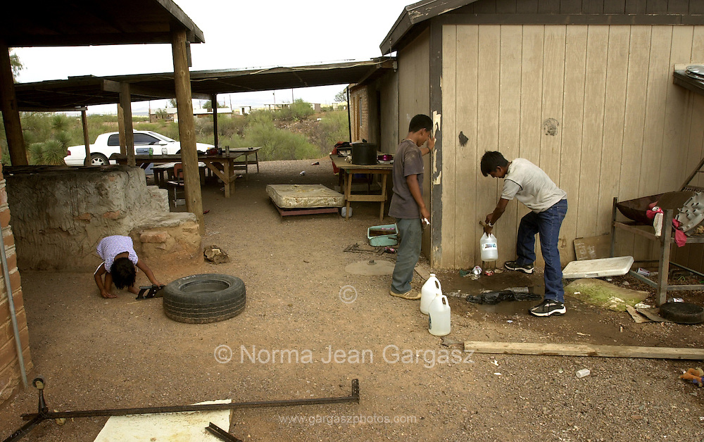 Illegal immigrants, who crossed from Mexico in to the United States on to the Tohono O'odham Nation in Arizona, refill water bottles at a residence before continuing to cross the Sonoran Desert, USA.