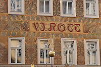 Prague old town: particular of decorated house. Wall in ocher color with four windows reflecting images of buildings on the other side of street.