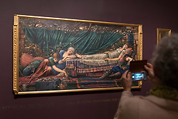 """© Licensed to London News Pictures. 22/10/2018. LONDON, UK. A visitor photographs """"The Rose Bower"""", 1886-90, part of the Briar Rose series, by Edward Burne-Jones.  Preview of the largest Edward Burne-Jones retrospective to be held in a generation at Tate Britain.  Burne-Jones was a pioneer of the symbolist movement and the only Pre-Raphaelite to achieve world-wide recognition in his lifetime.  The exhibition runs 24 October to 24 February 2019.  Photo credit: Stephen Chung/LNP"""