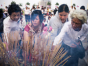"""31 JANUARY 2013 - PHNOM PENH, CAMBODIA: Cambodian women light incense for former King Norodom Sihanouk in front of the Royal Palace in Phnom Penh. Sihanouk (31 October 1922- 15 October 2012) was the King of Cambodia from 1941 to 1955 and again from 1993 to 2004. He was the effective ruler of Cambodia from 1953 to 1970. After his second abdication in 2004, he was given the honorific of """"The King-Father of Cambodia."""" Sihanouk served two terms as king, two as sovereign prince, one as president, two as prime minister, as well as numerous positions as leader of various governments-in-exile. He served as puppet head of state for the Khmer Rouge government in 1975-1976. Most of these positions were only honorific, including the last position as constitutional king of Cambodia. Sihanouk's actual period of effective rule over Cambodia was from 9 November 1953, when Cambodia gained its independence from France, until 18 March 1970, when General Lon Nol and the National Assembly deposed him. Upon his final abdication, the Cambodian throne council appointed Norodom Sihamoni, one of Sihanouk's sons, as the new king. Sihanouk died in Beijing, China, where he was receiving medical care, on Oct. 15, 2012. His funeral procession, which will wind through Phnom Penh is Friday, Feb.1 and his cremation is on Feb. 4, 2013. Over a million people are expected to attend the service.     PHOTO BY JACK KURTZ"""