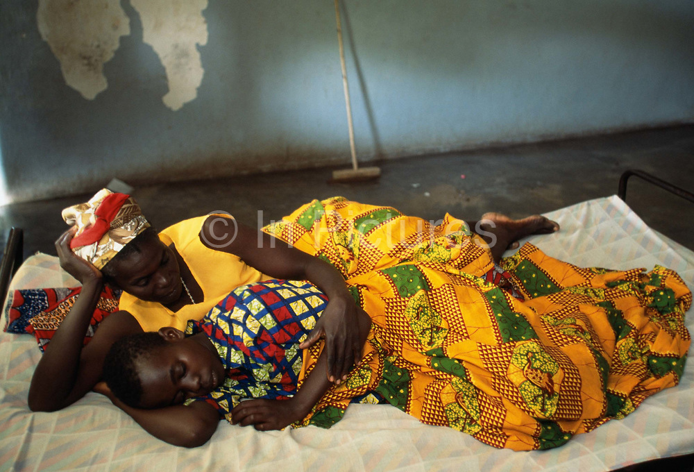 Alphonsine is held by her mother at the Kirarambogo Health Centre. It is likely that Alphonsine was infected by an uncle with whom she used to stay when she was a small child. Kibileze, Rwanda.