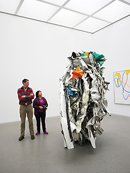 Visitors looking at sculpture Acme Thunderer by John Chamberlain at Pinakothek Moderne art museum in Munich Germany