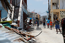 Residents wait in front of the houses destroyed by Irma during the visit of France's President Emmanuel Macron in the French Caribbean islands of St. Martin, Tuesday, Sept. 12, 2017. Macron is in the French-Dutch island of St. Martin, where 10 people were killed on the French side and four on the Dutch. Photo by Christophe Ena/Pool/ABACAPRESS.COM