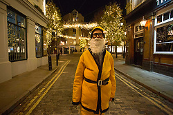 © Licensed to London News Pictures.24/11/2020. London, UK. A man dressed as Santa Claus in front of Christmas decorations at Seven Dials in central London, as England continues a four week national lockdown. Christmas Covid rules have been announced today, with five days of households mixing. Photo credit: Marcin Nowak/LNP