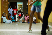 Children watch while models walk by during a rehearsal where models come to practice their catwalk in Ghana's capital Accra on Thursday May 21, 2009.