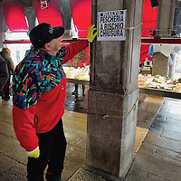 "VENICE, ITALY - FEBRUARY 08: A fishmongher reads a poster complaining about the possible closure of the historic Rialto Fish Market on February 8, 2011 in Venice, Italy. The Rialto Fish Market recently associated with the actor Johnny Depp because it appears in some scenes of the movie ""The Tourist"" risks closure if plans to move the fish wholesale market from Venice to Fusina go ahead."