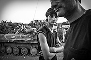 Father and son, Zaza and David Mezvrishvili, stand in front of a Russian tank blocking the highway. Igoeti.  August 15, 2008 .