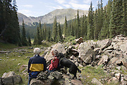 Two hikers with dog rest on hike in mountains of New Mexico.