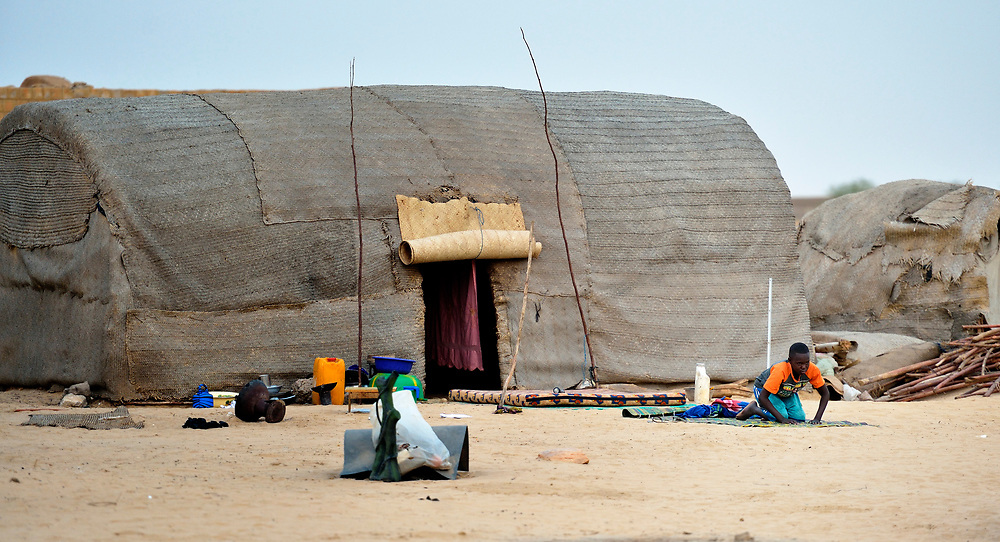 A young Muslim man prays in front of his family's tent in Timbuktu, a city in northern Mali which was seized by Islamist fighters in 2012 and then liberated by French and Malian soldiers in early 2013. He belongs to the Bella ethnic group, which has traditionally been exploited by Timbuktu's lighter-skinned groups.