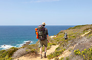Two people walking the cliff top coastal long distance footpath trail, The Fisherman's Walk or Ruta Vicentina,  near Odeceixe, Algarve, Portugal, Southern Europe