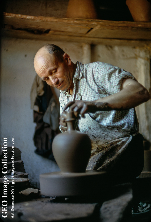 Potter creates a graceful jar out of clay.