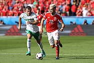 Aaron Ramsey of Wales breaks past Aaron Hughes of Northern Ireland. UEFA Euro 2016, last 16 , Wales v Northern Ireland at the Parc des Princes in Paris, France on Saturday 25th June 2016, pic by  Andrew Orchard, Andrew Orchard sports photography.