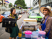 18 FEBRUARY 2015 - BANGKOK, THAILAND: A student at Santa Cruz Catholic school buys a crushed ice dessert from a street vendor in the Kudeejeen neighborhood in Bangkok. Santa Cruz church was established in 1770 and is the heart of the community. It is one of the oldest and most historic Catholic churches in Thailand. The church was originally built by Portuguese soldiers allied with King Taksin the Great. Taksin authorized the church as a thanks to the Portuguese who assisted the Siamese during the war with Burma. Most of the Catholics in the neighborhood trace their family roots to the original Portuguese soldiers who married Siamese (Thai) women. There are about 300,000 Catholics in Thailand in about 430 Catholic parishes and about 660 Catholic priests in Thailand. Thais are tolerant of other religions and although Thailand is officially Buddhist, Catholics are allowed to freely practice and people who convert to Catholicism are not discriminated against.   PHOTO BY JACK KURTZ