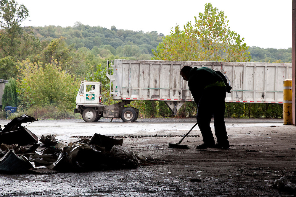 Man sweeps tipping floor of waste transfer station with waste transfer truck in background