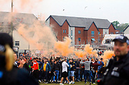 The air turns orange as Newport County fans invade the pitch in celebration at the end of the game after seeing their side survive in League 2. EFL Skybet football league two match, Newport county v Notts County at Rodney Parade in Newport, South Wales on Saturday 6th May 2017.<br /> pic by David Richards, Andrew Orchard sports photography.