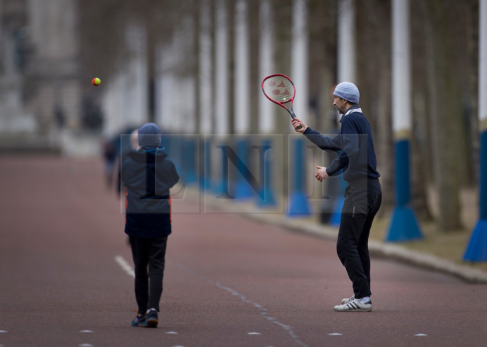 © Licensed to London News Pictures. 21/02/2021. London, UK. A man is watched by his son as he plays a quick game of tennis in a nearly deserted Mall in sight of Buckingham Palace in central London. Temperatures reached 14 C in parts of the south today. Photo credit: Peter Macdiarmid/LNP
