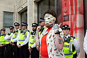 With a mask clad and tattooed demonstrator making a gesture in front of them, police at an Extinction Rebellion protest line up in a row outside Guildhall, which has been covered in red paint to signify blood, on 27th August, 2021 in London, United Kingdom. The activist group Extinction Rebellion XR are planning actions of disruption for two weeks straight beginning on August 23rd, 2021 in an effort to bring awareness and priority to the global climate emergency in advance of the COP 26 Summit which will be held in Glasgow later this year.