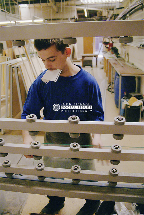 Man working in glass factory operating machinery,