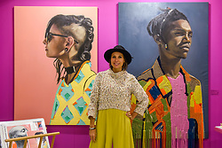 """© Licensed to London News Pictures. 05/10/2019. LONDON, UK. Artist Athena Anastasiou poses with two of her works (L to R) """"The Modern Muisca"""", 2019, and """"Bringing the Past to New Horizons"""", 2019, at The Other Art Fair, presented by Saatchi Art.  120 international, independent artists are displaying their works to be sold direct to buyers.  The fair is taking place at Victoria House in Bloomsbury until 6 October 2019.  Photo credit: Stephen Chung/LNP"""