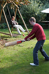 Young men with autism on swing in garden and playing cricket. Cleared for Mental Health issues.